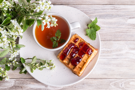 A cup of tea and waffles on an open background.