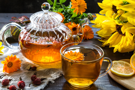 Tea with marigold and dog rose on a dark wooden background. Reklamní fotografie - 123219556