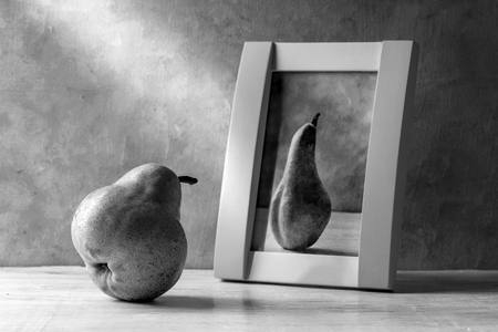 The thick pear admires a portrait of a slender pear.