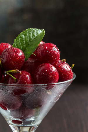 Fresh sweet cherry with water drops in a transparent glass. Imagens