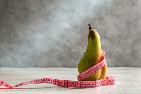 Pear and measuring tape on a gray background. Imagens