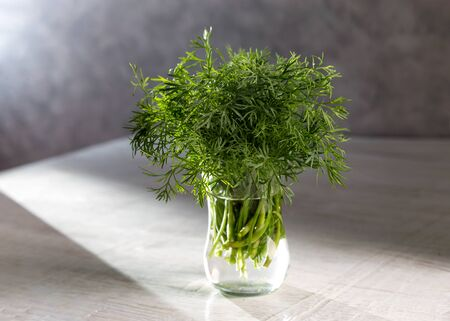 Dill in a transparent vase on a wooden table. Stok Fotoğraf