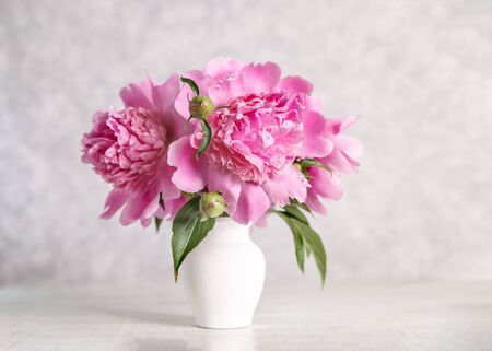 Bouquet of pink peonies in a vase on a wooden table. Gift Valentines Day.