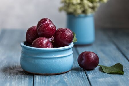 Plums in a blue bowl on a wooden background.