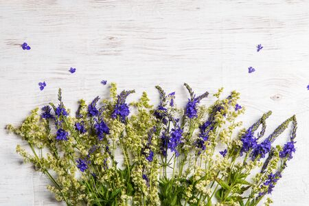 Bouquet of wildflowers on a wooden background. Copy space for the text.