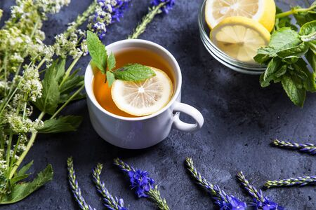 Hot tea with mint lemon in a white cup on a dark background.