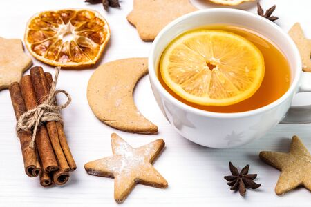 Lemon tea, gingerbread, cinnamon and dried oranges on a bright background.