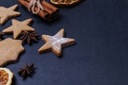 Gingerbread, cinnamon and dried oranges on a dark background. Copy spase.