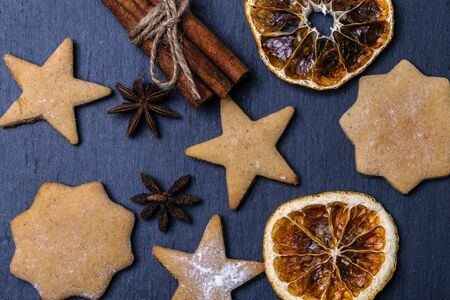 Gingerbread, cinnamon and dried oranges on a dark background.