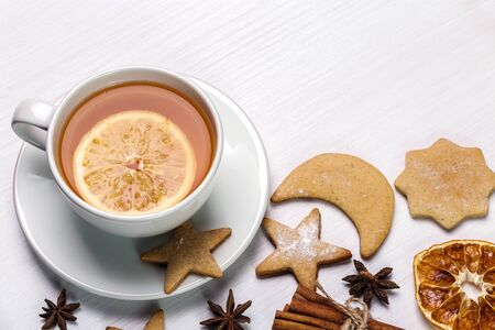 Lemon tea, gingerbread, cinnamon and dried oranges on a bright background. Copy space.