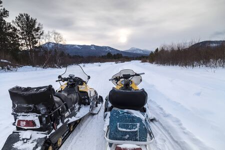 Two snowmobiles on the road in the mountains of the Urals.