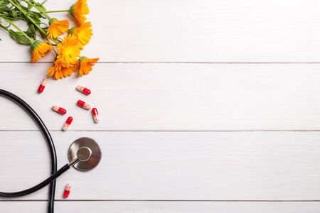 Stethoscope, pills and calendula flowers on a wooden background.