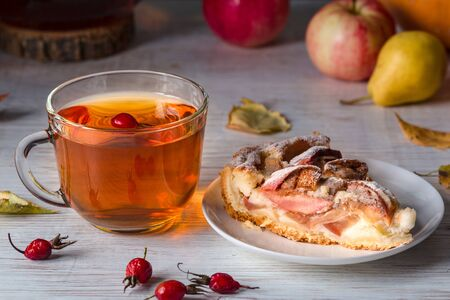 Tea and pie with apples on a light table. Фото со стока