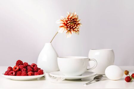 Still life. White breakfast with raspberries on a white background.