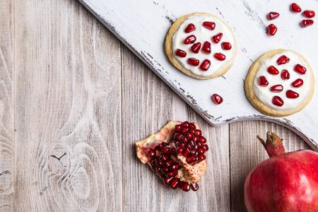 Crumbly cookies with yogurt cream garnished with pomegranate seeds.