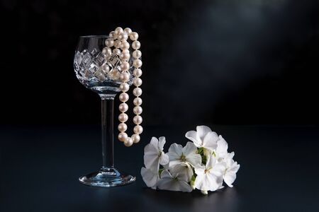 Beads from pearls in a glass, on a dark background.