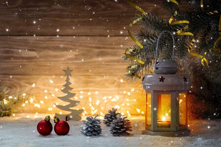 Lantern candlestick and Christmas decorations on a wooden background. Copy space.