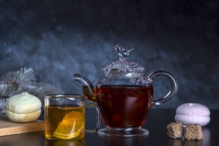Hot tea with lemon in a transparent bowl and marshmallows on a dark background.