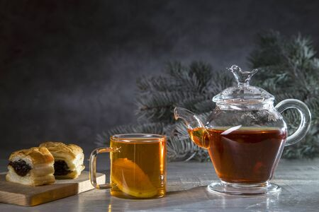 Hot tea with lemon in a transparent bowl and a croissant on a dark background.