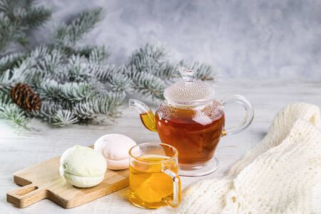 Hot tea with lemon in a transparent bowl and marshmallows on a light background.