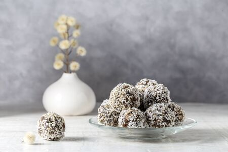 Healthy homemade sweet balls of dried fruits and nuts in coconut.