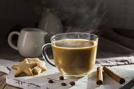Coffee with milk and cinnamon on a wooden table.