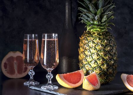 Sparkling wine and pineapple with grapefruit on a dark background.