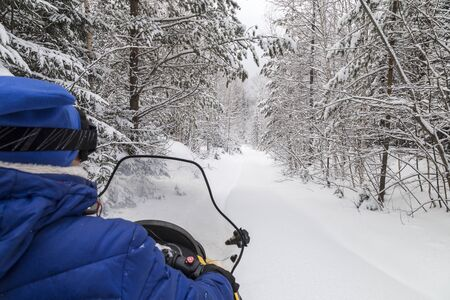 The girl on a snowmobile  in the mountains of the Urals.