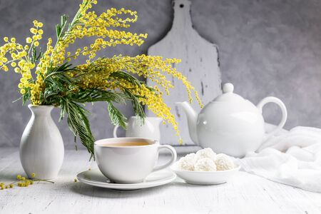 A bouquet of mimosas in a vase with tea and candies on a light background. Archivio Fotografico