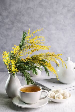 A bouquet of mimosas in a vase with tea and candies on a light background.