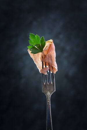 Bacon and parsley leaf on a fork on a dark background.