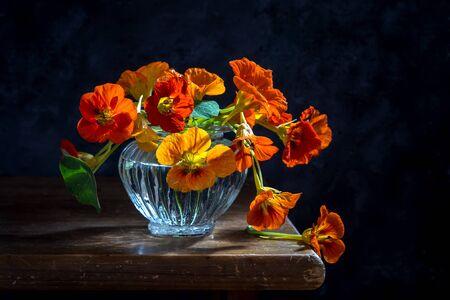 Bouquet of nasturtiums in a glass vase on a dark background.