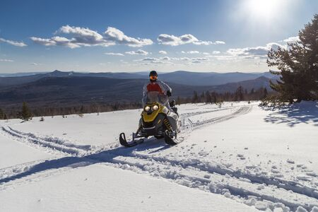 Athlete on a snowmobile moving in the winter forest in the mountains of the Southern Urals.