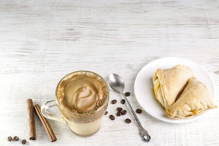 Iced Dalgona Coffee, fashionable fluffy creamy whipped coffee on a light background.