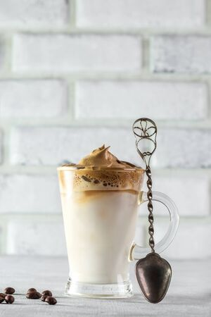 Iced Dalgona Coffee, fashionable fluffy creamy whipped coffee on a light coloured background.