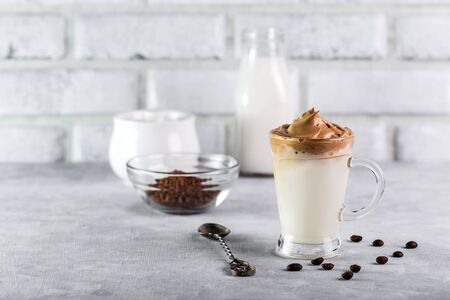 Iced Dalgona Coffee, fashionable fluffy creamy whipped coffee on a light coloured background. Фото со стока