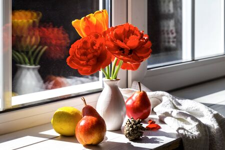 Bouquet of tulips and pears with lemon on the windowsill.