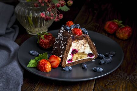 A serving of chocolate cake with curd filling, honeysuckle and banana, sprinkled with strawberries and honeysuckle.