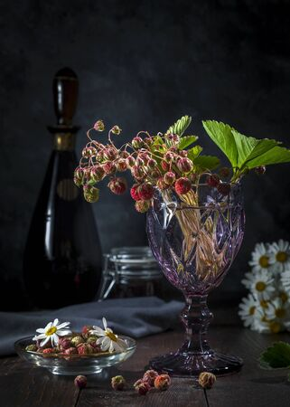 A bouquet of forest strawberries in a glass, on a dark background. Zdjęcie Seryjne