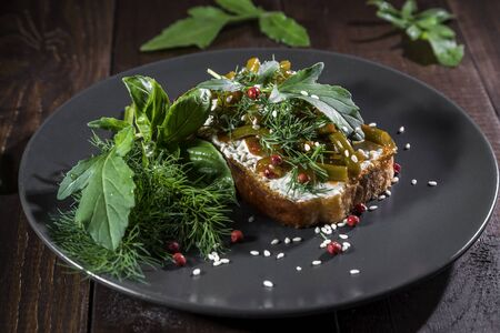 Toast with curd cheese, fried garlic arrows and herbs on a dark background.