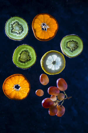 Slices of fruit on a dark background in the backlight. 免版税图像