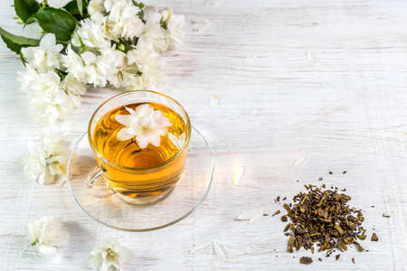 Jasmine tea in a cup on a wooden background. Reklamní fotografie