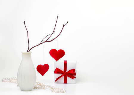A vase of hearts hanging from a branch and a Valentine's Day gift. Copy space.