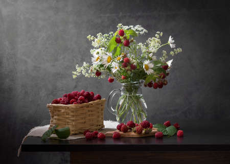 Still life with raspberries and a bouquet of daisies. Stock Photo