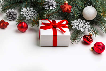 Christmas decorations and a gift in a box lying on a white background. Copy space. Stock Photo