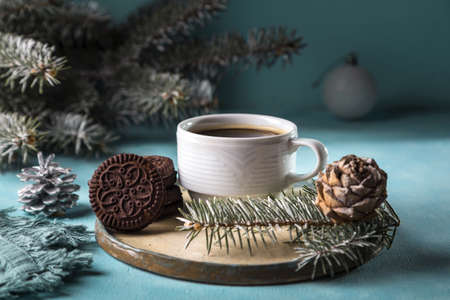 Hot coffee in a white mug. Christmas time. Cozy home atmosphere, blue background. Stock Photo