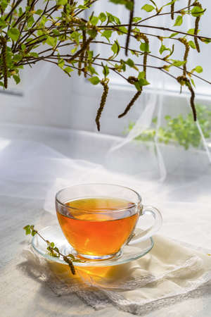 Tea in a transparent cup and a bouquet of spring birch branches on the windowsill. Stock Photo