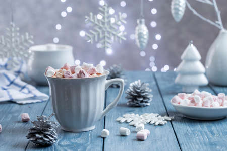 Cup of delicious hot cocoa with marshmallows on a blue wooden background and Christmas decorations.