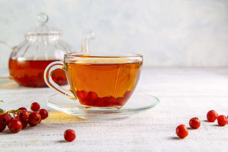 Hot tea with hawthorn in a transparent cup and a teapot with tea on a light background.