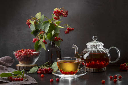 Hot tea with hawthorn in a transparent cup and a teapot with tea on a dark background.